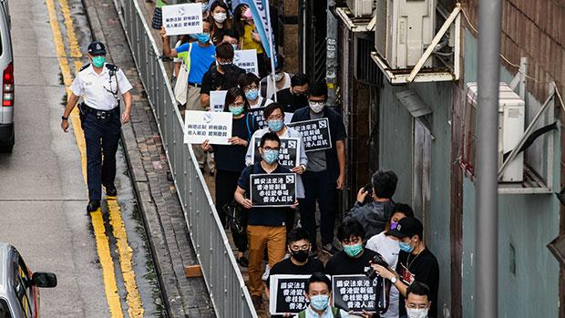 2020年5月22日,示威者手持反對「港版國安法」的標語遊行至香港中聯辦。(法新社)