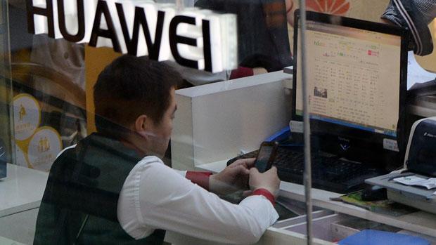 2014年3月24日,北京華為專門店內,一名華為員工正在檢查電話設備。(法新社)