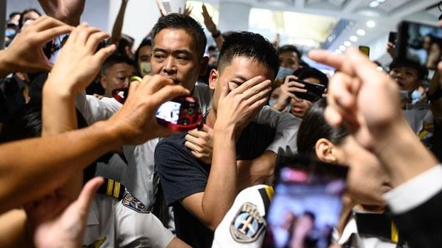 一名疑似大陆便衣公安,周二(13日)在香港国际机场出现引发混乱。(AFP)
