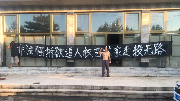 2018年8月8日,北京人權藝術家王鵬在位於北京平谷區的工作室門前拉橫幅抗議強拆。(吳亦桐提供)