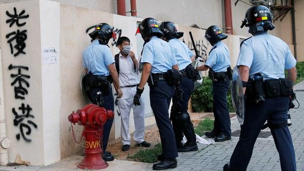 2019年10月8日,在香港,一名戴口罩的学生在校外被警察包围。(路透社)