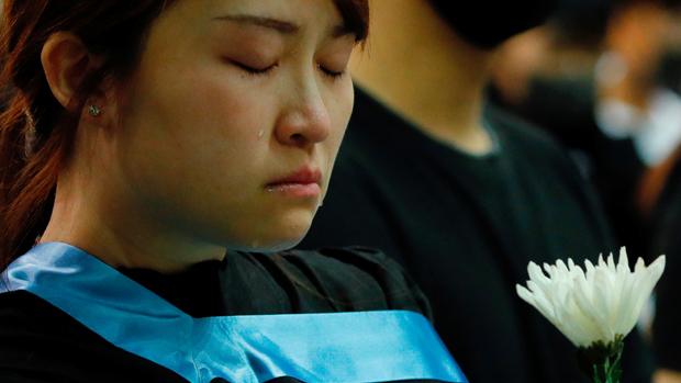 一名科大畢業生周五(8日)得悉周梓樂死亡後,傷心落淚。(路透社)