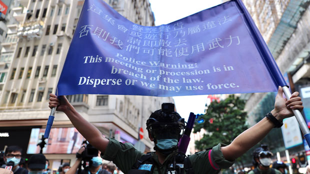 2020年10月1日,香港警察舉旗要求遊行人士散退,警告警方可能採用武力。(法新社)