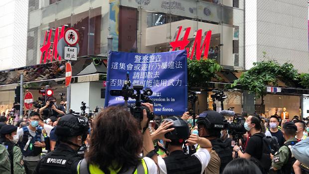 警方高舉藍旗指現場屬非法集會。(文海欣 攝)