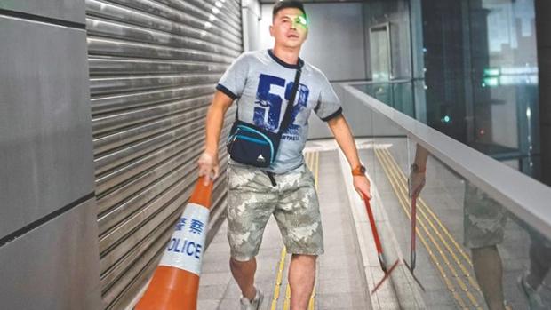 警員張金福庭上稱被打爆痱滋,痛了一星期。圖為張金福去年6月26日手持水刮及警察雪糕筒衝入警總。(香港蘋果日報圖片)