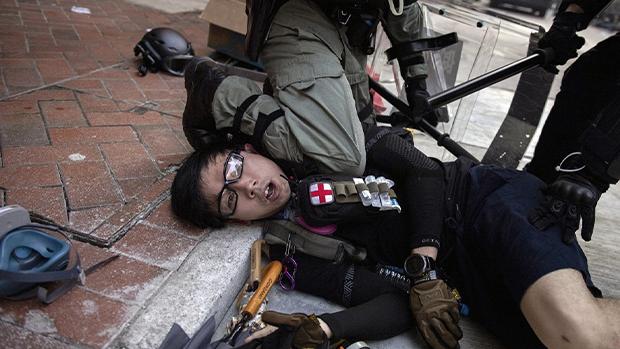 香港警察於去年10月1日在灣仔跪壓年輕急救員頸部。照片由法新社記者阿斯弗里拍攝。(法新社)