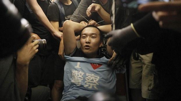 大陆官媒《环球时报》记者付国豪,在香港机场被示威者怀疑是便衣公安,将他非法禁锢及殴打事件,被官方大肆评击后突然紧急降温。(AP)